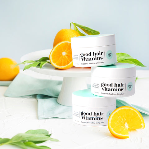 Trico.Lab Good Hair Vitamins stacked on top of each other with oranges and mint around it
