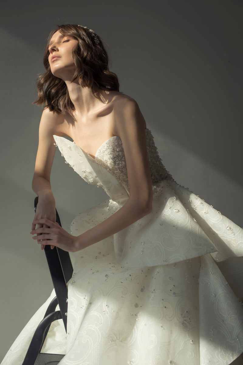 Long strapless lace beaded dress, with a draping on top and peplum on waist down.