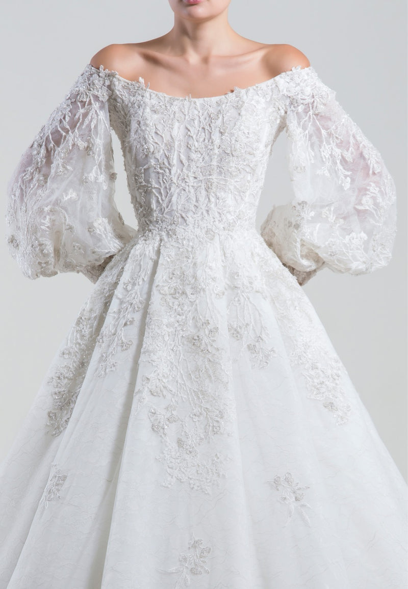 Long off-shoulder embroidered dress, with wide embroidered sleeves, cuffs and a pleated skirt.