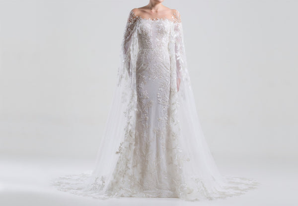 Long fully beaded tulle dress with a round	tulle	neckline,	and a beaded	cape.