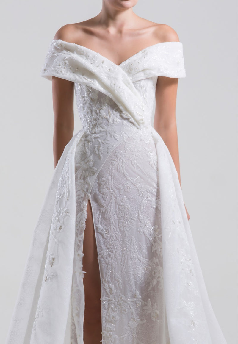 Long off-shoulder wrapped beaded dress, with a slit and an overskirt.