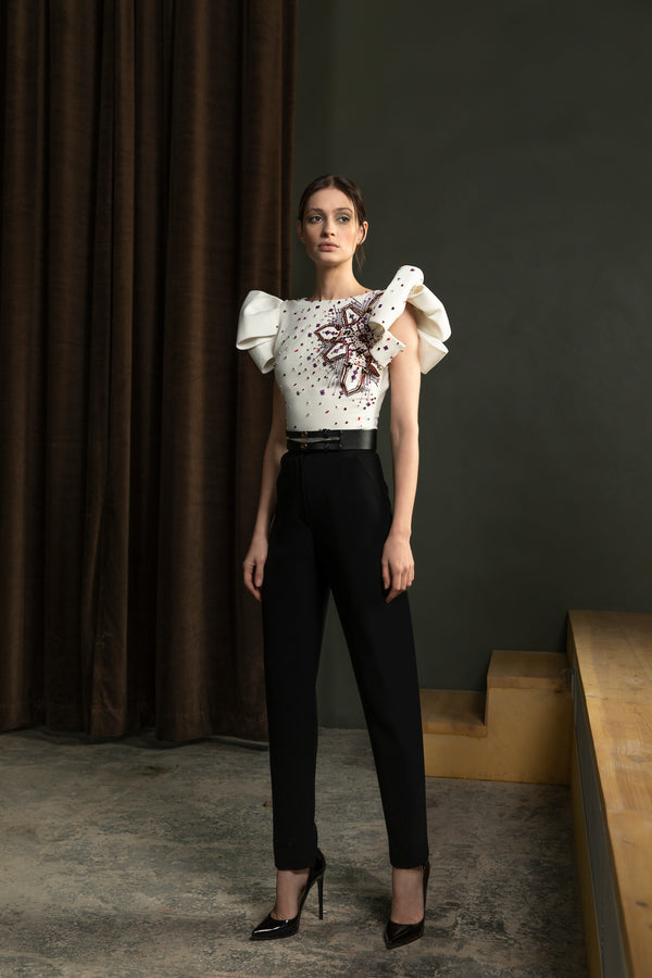 Beaded sleeveless, crepe marocain bodysuit and classic	 crepe pants with straight legs and a wide	leather belt