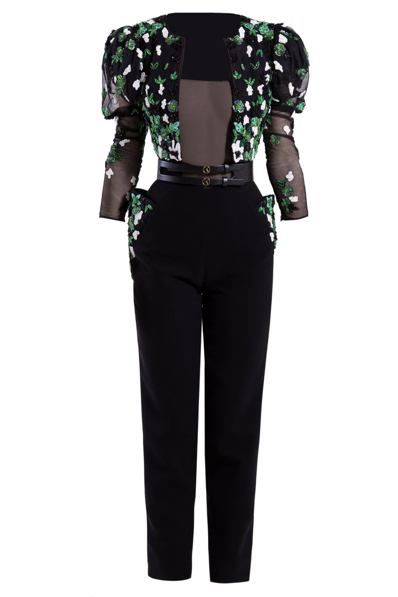 Crepe marocain black jumpsuit with a black tulle top and beaded side pockets, paired with a beaded tulle jacket and a signature black leather belt.