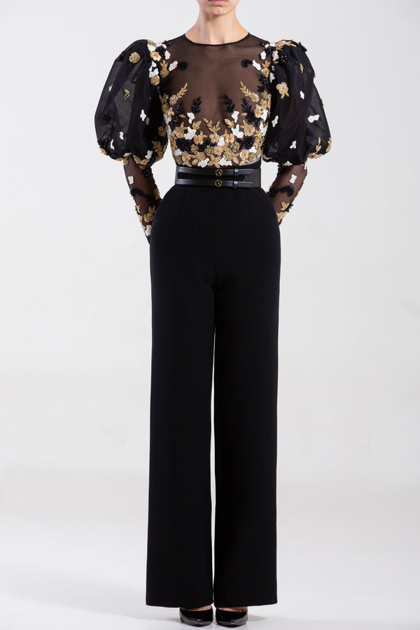 Crepe marocain jumpsuit with a tulle beaded top and sleeves, paired with a signature black leather belt.
