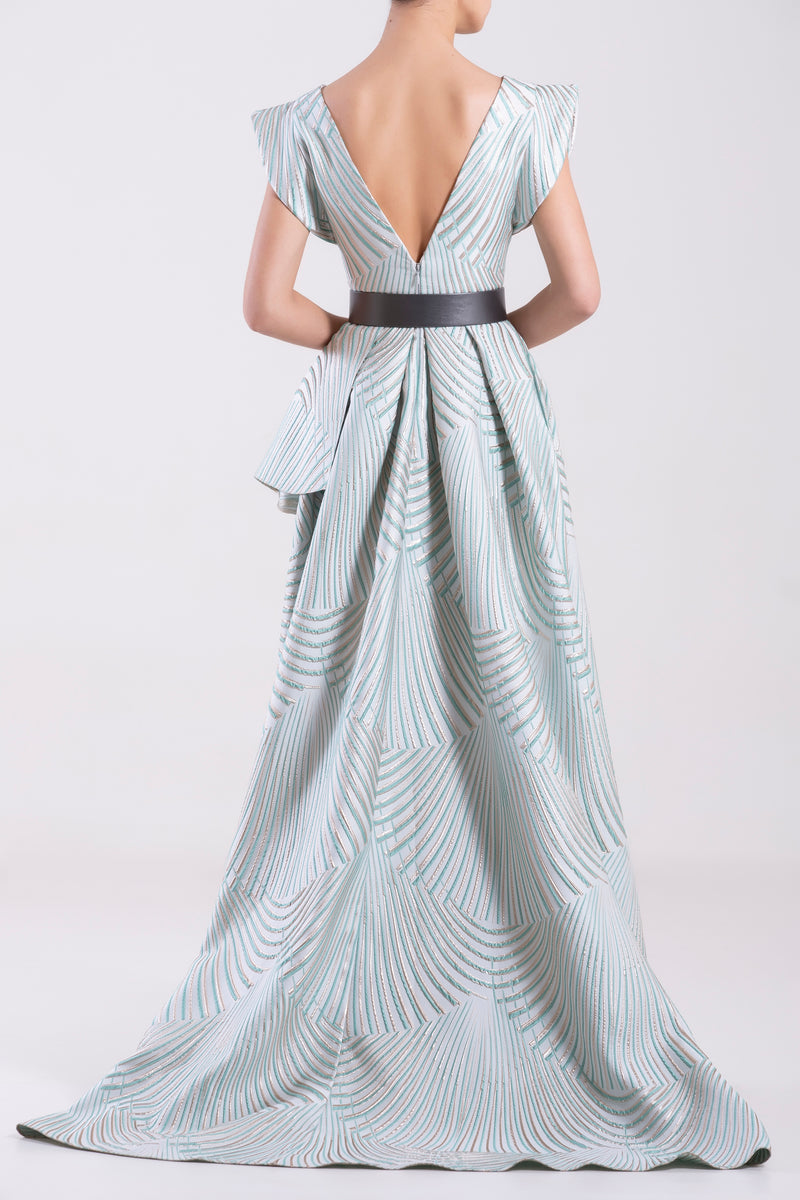 Long Brocade Blue Tint flared dress with an asymmetrical skirt, paired with a metallic grey leather belt.