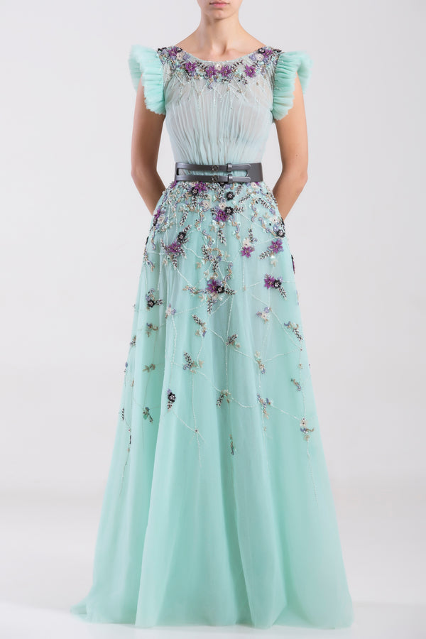 Long tulle Blue Tint beaded dress with pleated short sleeves, paired with a metallic grey leather belt.