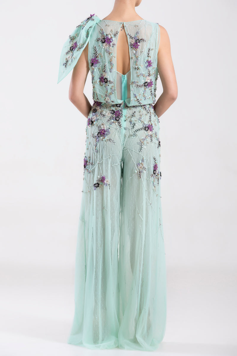 Tulle Blue Tint, sleeveless beaded jumpsuit with a beaded ruffle on one shoulder and a slit on the back.