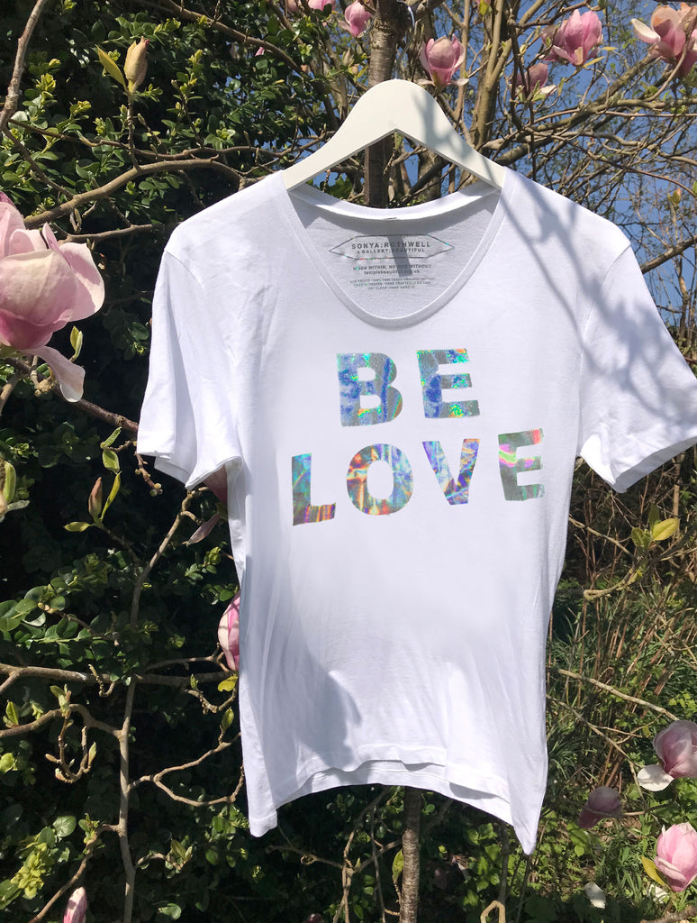 100% Non-Profit Holographic Slogan 'BE LOVE' Unisex T-Shirt designed by Sonya Rothwell x Temple Beautiful : Made in Heaven, hand printed in Britain to order on pure organic Fair Trade cotton with a stylish wide scoop neck : Modelled by Masai + Samburu Warriors, Kenya