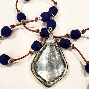 Navy blue beach glass on natural brown knotted leather. Silver leaf leaded pendant