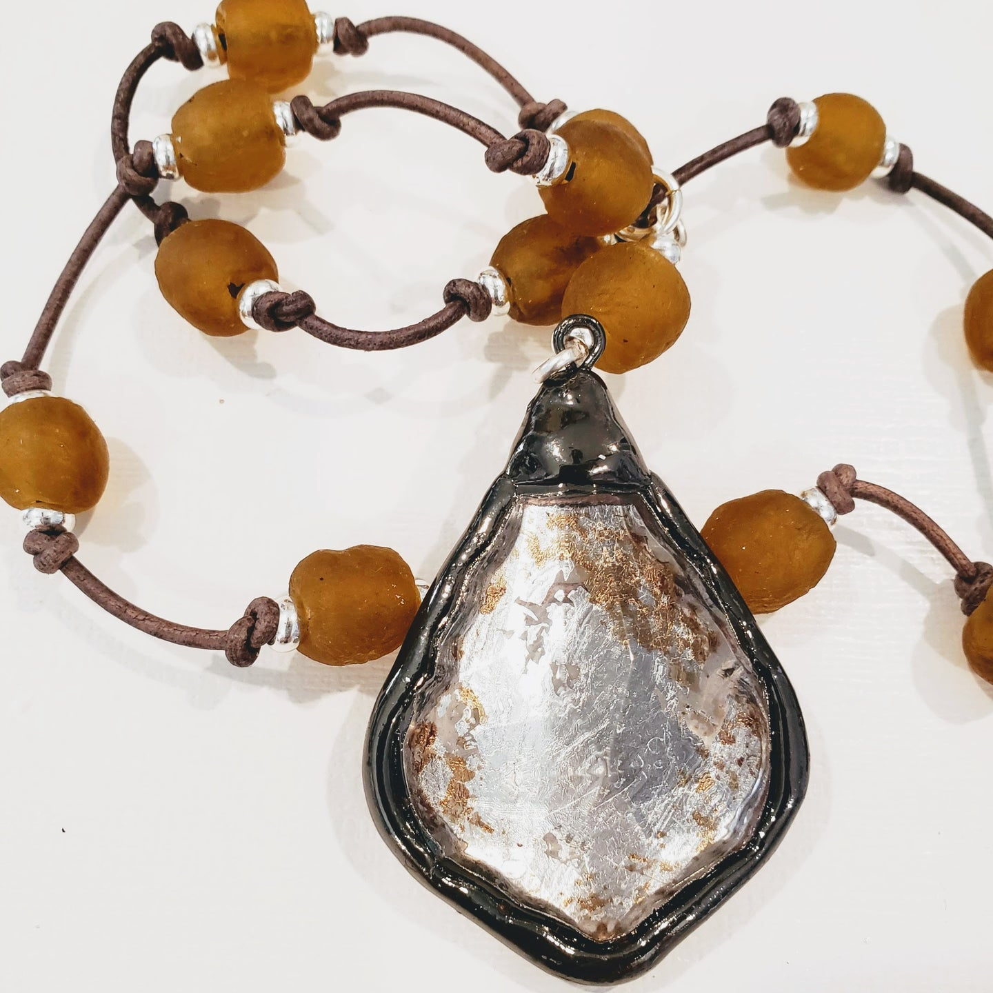 Amber beach glass on natural brown knotted leather.  Silver leaf