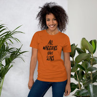 "African American woman wearing a burnt orange autumn colored inspirational ""All Warriors Have Scars"" graphic tee - created by EMPOWERHAUS artist and breast cancer survivor, Emily Hopper."