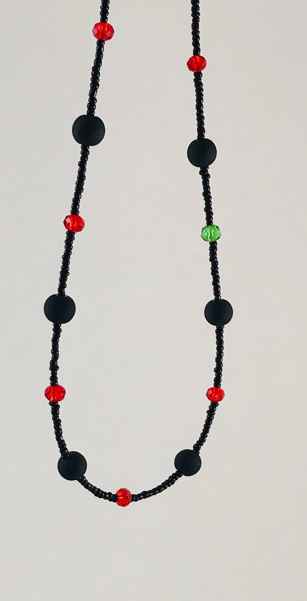 black and red glass bead necklace with contrasting green glass bead
