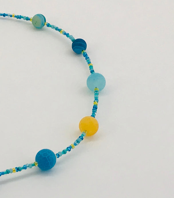 blue glass bead necklace with contrasting yellow glass bead