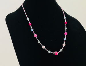 pink and white glass bead necklace with paw charm