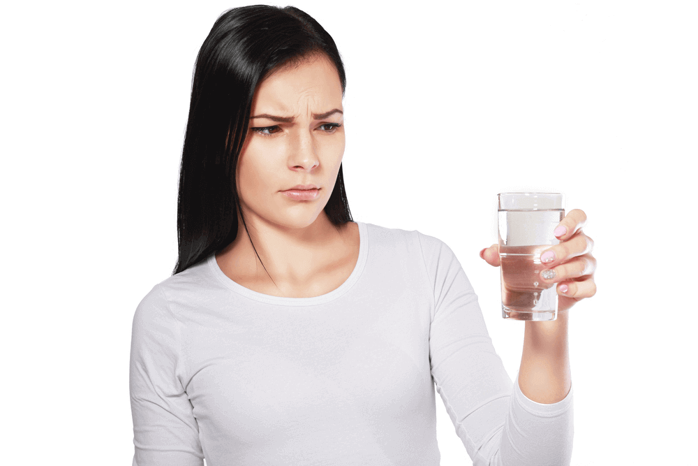 A female looks doubtful to the glass of water she's holding