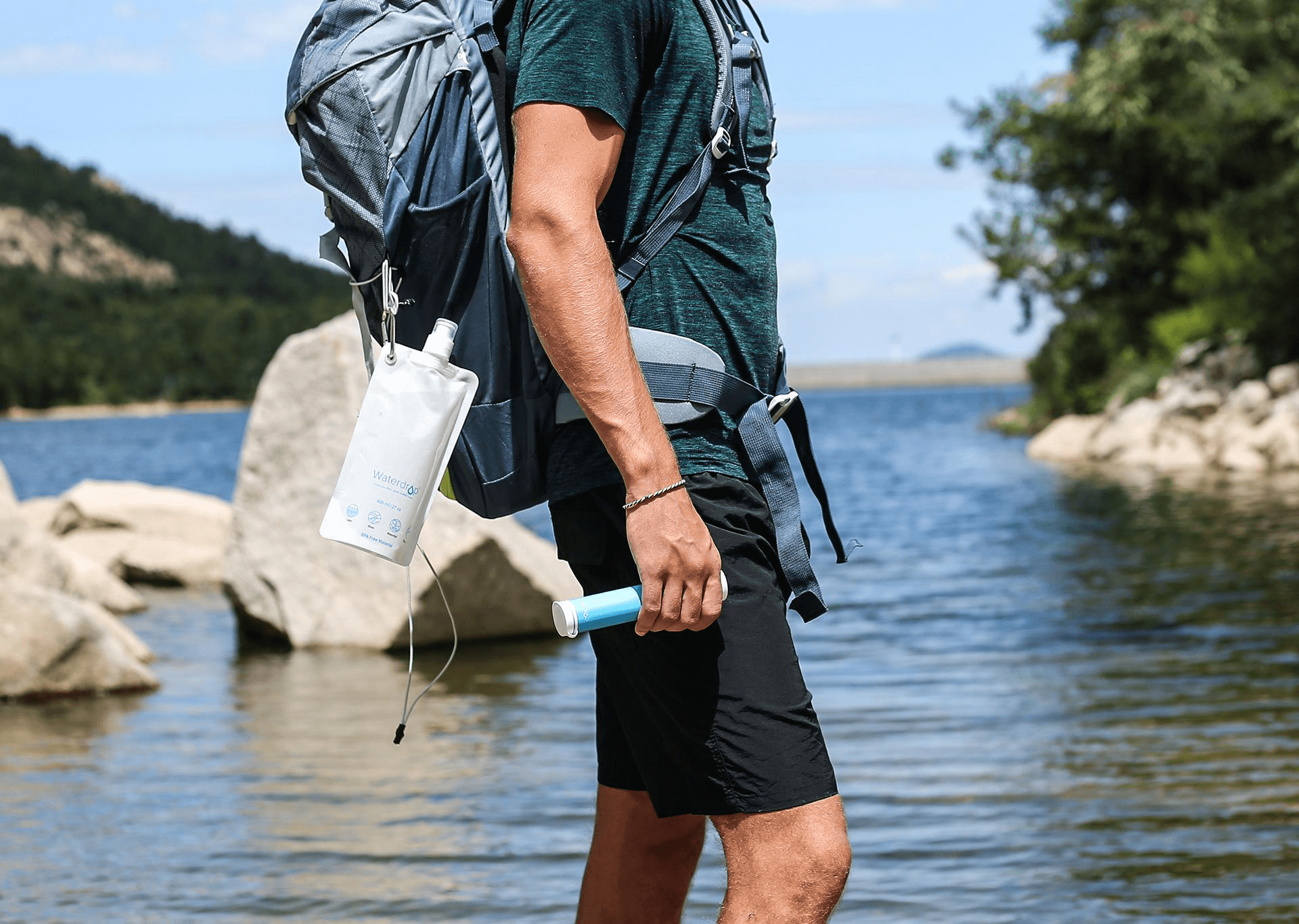 A person walking by the river holding a water filter straw in his right hand and a water pouch hanging on his backpack