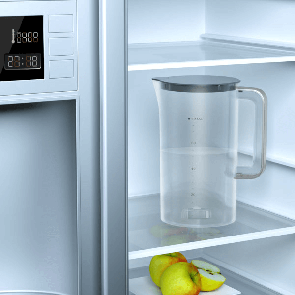 The water pitcher filled with water and being placed inside the refrigerator