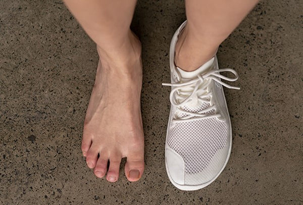 A pair of feet, one without a shoe and the other wearing a Vivobarefoot shoe
