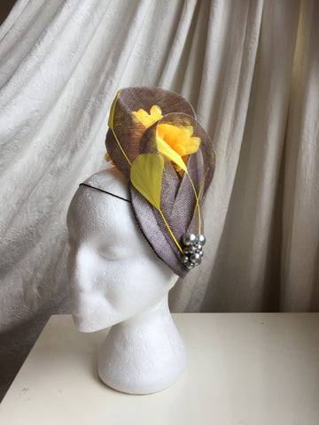 Grey and lemon headpiece, hat, punchestown , ascot, horse racing, ladies day headpiece, teardrop base in grey, with lemon flower and lemon feather details, grey pearl jewel cluster, sinamay swirls, little rose design original millinery