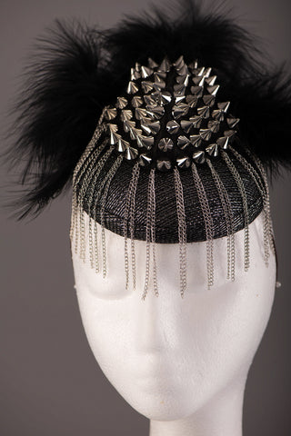 ryk chick headpiece, A black and silver sinamay base with silver stud work, soft black feathers and thin silver chains creating an avant garde fringe effect.A gorgeous edgy piece great for magazine/editorial work.