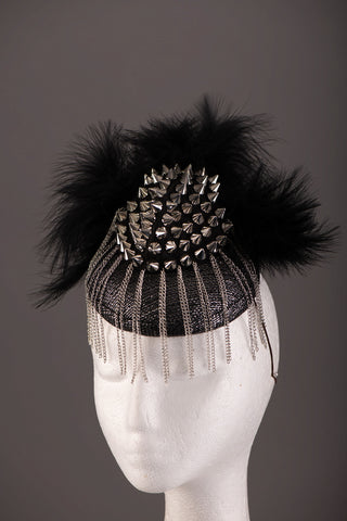 Rock chick headpiece, A black and silver sinamay base with silver stud work, soft black feathers and thin silver chains creating an avant garde fringe effect.A gorgeous edgy piece great for magazine/editorial work