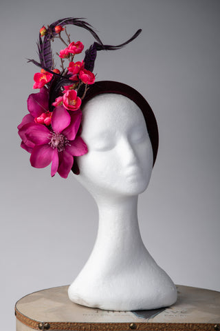 magenta, pink and purple crown headband style headpiece.For weddings, special occasions, horse racing events. The headpiece has pheasant feathers and cherry blossom added to large magenta flowers.