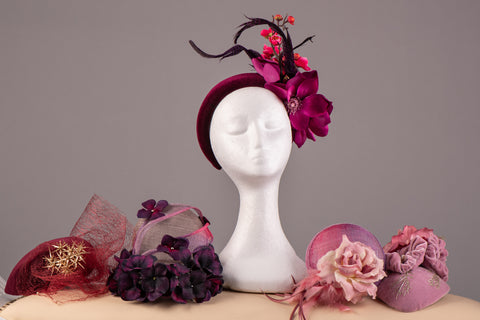 A selection of handmade hats and headpieces in soft pinks and magenta, with a centre crown on a mannequin , all made by Little Rose Design, wedding hat and fascinator specialist.Expert milliner, millinery.