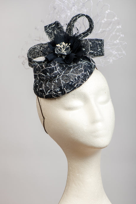 Dark navy and white headpiece with waffle veiling.
