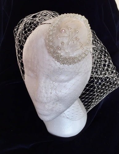 Satin pearl and feather bridal headpiece with birdcage.