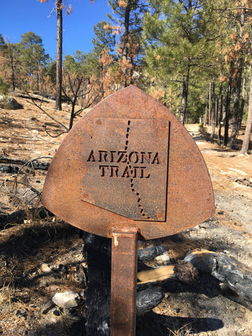 "Rusted sign reads ""Arizona Trail"" with the shape of Arizona state showing the trail going across the state"