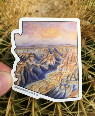Vinyl sticker the shape of Arizona with a watercolor scene of the Grand Canyon at sunset with a pink/purple sky and deep shadows in the canyon with orange sun highlights