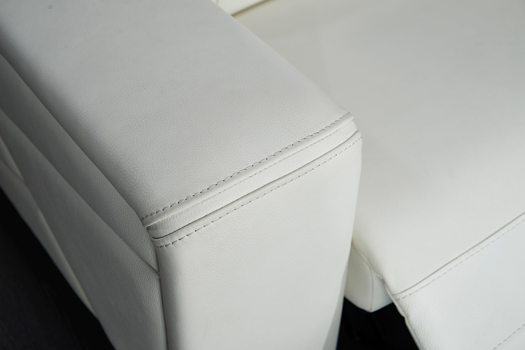 white leather electric recliner chair arm closeup
