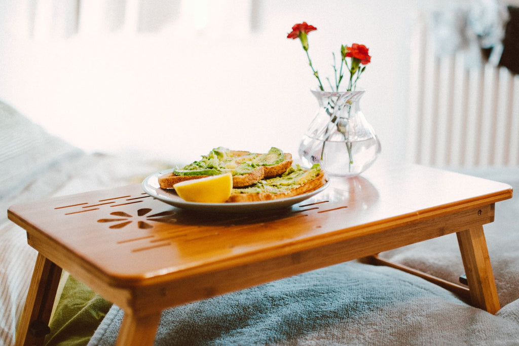 breakfast in bed avocado toast with flowers on tray