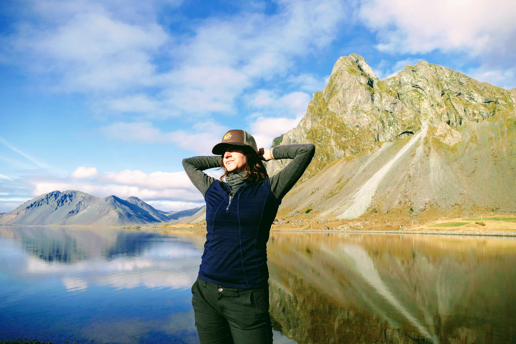 woman in front of serene lake and mountains adjusting hair and wearing bug out bar cricket protein hat