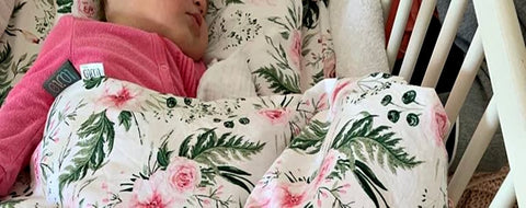 baby sleeping under the pink blossom blanket