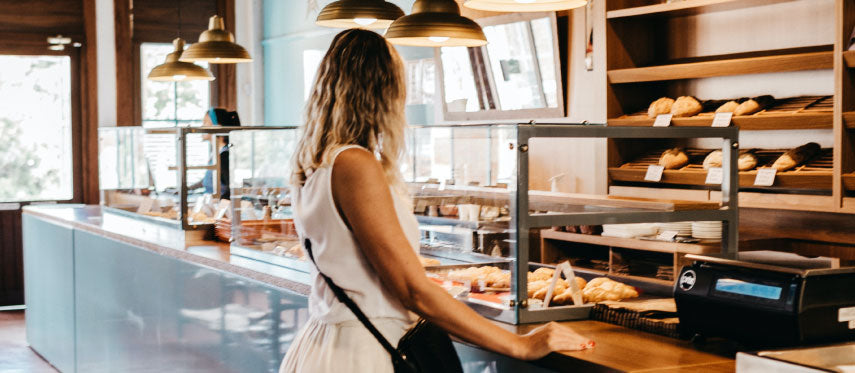 Woman looking at coffee shop pastries