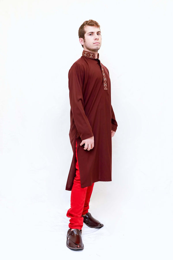 A dark red cotton shirt with tan embroidering around the neckline