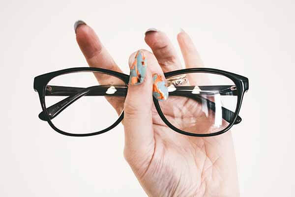 Someone holding a pair of glasses