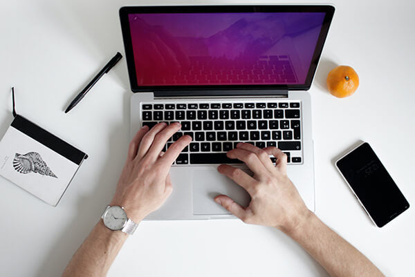 Two hands typing on a computer keyboard