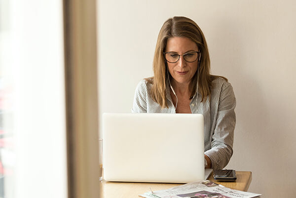 A woman is wearing anti-blue glasses for computer work to protect her eyes.