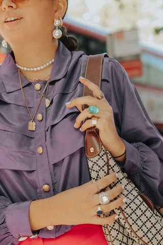 Street Style: Pearl earrings, minimal layered gold pendant chains, and boho rings