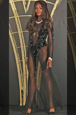 Naomi Campbell wearing diamond layered necklace and bracelet and long gold pendant chain at LFWSS20