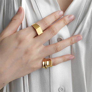 A Hand Wearing Chunky Gold Plated Statement Rings