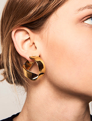 Fashion model wearing the 18k gold plated twirl hoop earrings handmade from stainless steel