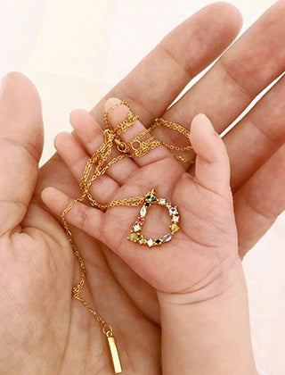 A child's hand holding the 18k Gold plated personalized multi-stone letter 'D' Pendant necklace