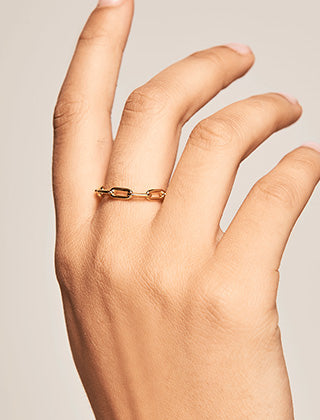A hand wearing the minimal gold plated chain link cyclone ring