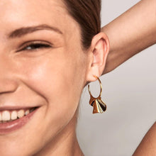 Load image into Gallery viewer, A girl smiling wearing 18k Gold plated handmade pair of wavy motif hung on hoop earrings