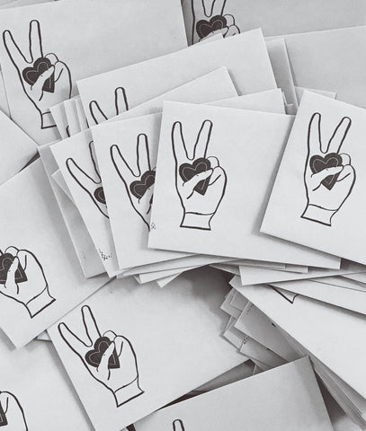 Hand Stamped Envelopes with Peace Sign holding a Heart is Amador Collective's Signature Envelope Style