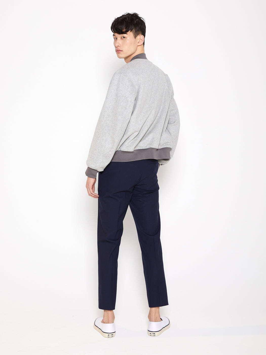 Model wearing Men Reversible Wool Patch Bomber in Stone Grey/ Melange Grey (Stone Grey Back View)