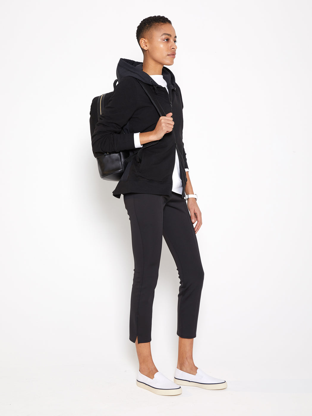 Model wearing Women Back Pleated Hoodie Zip-Up made with Organic Cotton in Black (Side View)